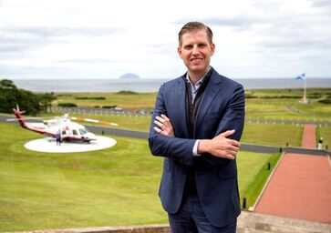 Headshot of Eric Trump, with helicopter in background