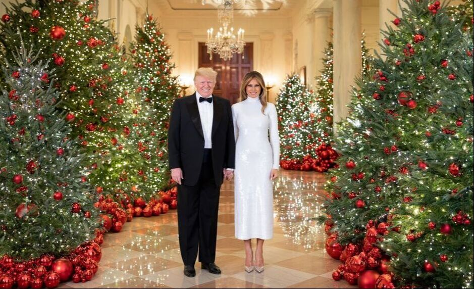 President Donald Trump, stands with first lady Melania, surrounded by Christmas trees, in the White House
